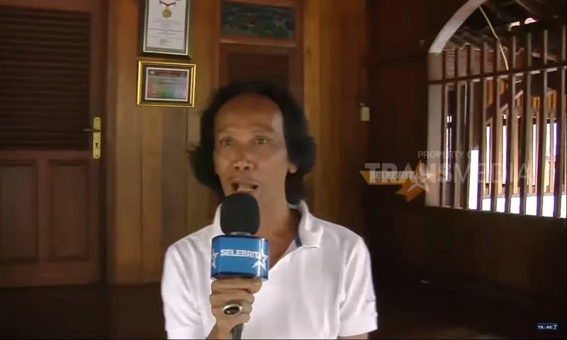 Mandra yang di wawancarai di bangunan khusus miliknya yang dijadikan tempat berkumpul saudara hingga tetangga